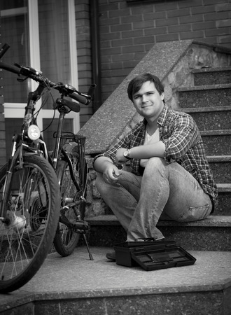 maintaining: Black and white photo of young man maintaining his bicycle