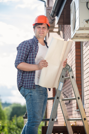 Young electrician standing on high stepladder and holding plan of house