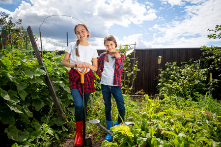 gum boots: Two beautiful teenage girls working in garden at sunny day