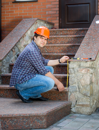Young contractor worker measuring stone staircase with measuring tape Stock Photo