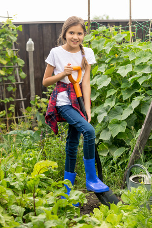 Happy young girl working at garden with shovel