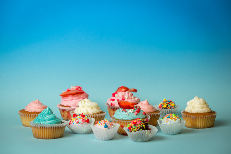 Closeup photo of different tasty sweets on blue background
