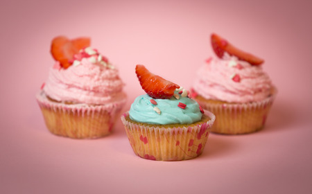 Macro shot of three decorated cupcakes with blue and pink buttercream Stock Photo