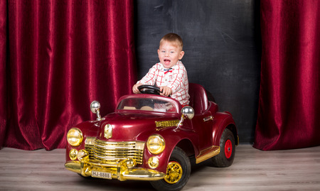 nappy new year: Studio image of cute baby posing in big toy car at studio Stock Photo