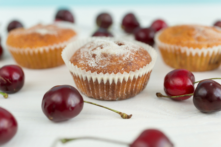 gateau: Macro photo of muffins with cherry on white table Stock Photo