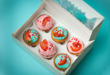 Foto de detalle de la caja de papel abierta con seis pastelitos de colores Foto de archivo - 62632344