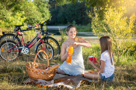 10 years: Happy young woman having picnic by the river with 10 years old daughter. Two bicycles on the background