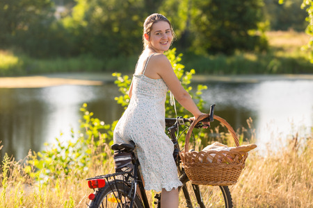 Portrait of beautiful young woman in short dress riding on bicycle by the lake at sunset