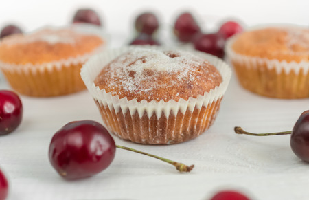 Closeup photo of muffin decorated with powdered sugar and cherries Stock Photo