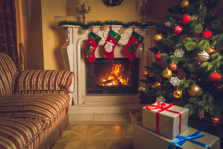 hearthside: Toned interior image of living room with burning fireplace, decorated Christmas tree and stack of gifts