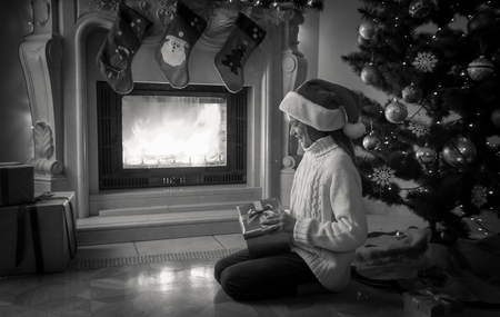 desaturated: Black and white image of girl holding gift box and sitting next fireplace and decorated Christmas tree