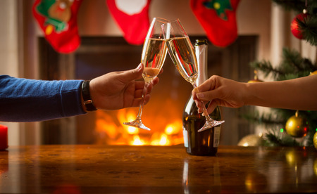 Primo piano di uomo e donna celebrare il Natale e tintinnano, bicchieri con champagne a camino