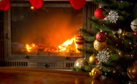 christmas backdrop: Beautiful decorated Christmas tree next to burning fireplace with natural logs Stock Photo
