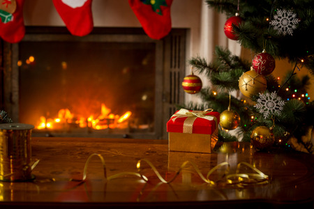 indoor background: Christmas background with red gift box on wooden table in front of burning fireplace and Christmas tree. Empty place for text Stock Photo