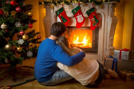 Jong paar in liefde zittend op de vloer en kijken naar open haard en versierde kerstboom