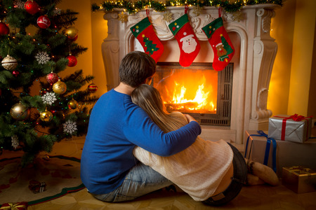 Young couple in love sitting on floor and looking at burning fireplace and decorated Christmas tree 免版税图像