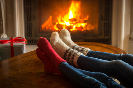 cosy: Toned image of couple wearing woolen socks relaxing by the fireplace at house Stock Photo
