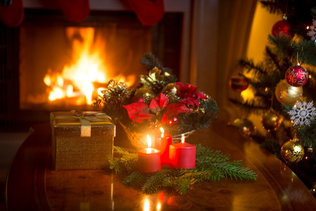 burning christmas tree by the fireplace and golden gift box stock photo 65356133