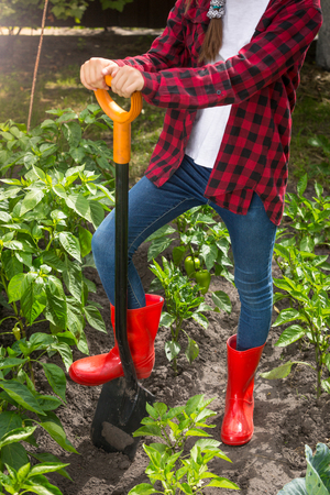Closeup young woman in red wellington boots working on garden bed with shovel Stock Photo