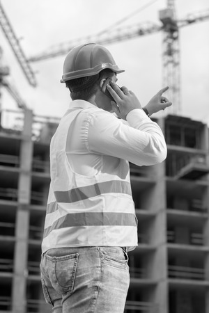 Black and white rear view image of construction engineer talking by phone and pointing at building site