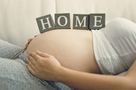 fondling: Closeup image of pregnant woman holding word Home on belly Stock Photo