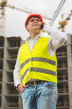 Young smiling engineer in hardhat and safety vest talking by phone on building site Stock Photo