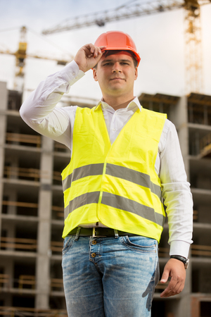Handsome smiling engineer in hardhat posing against working construction crane Stock Photo