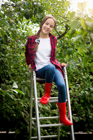 Young girl in red wellington boots  sitting on stepladder at garden