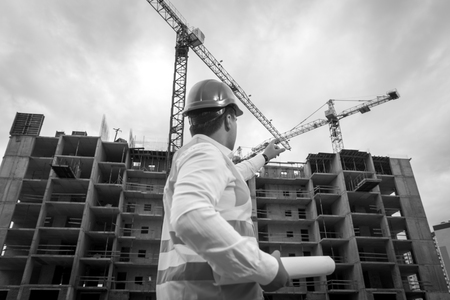 Black and white image of young engineer holding blueprints and pointing at building site with hardhat