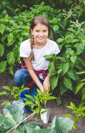 Bela adolescente sorridente, trabalhando no jardim com pá de mão Foto de archivo - 81038452