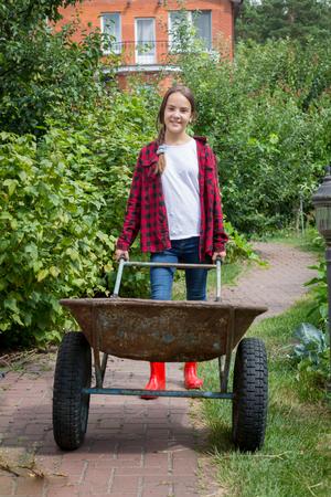 paysagiste: Jeune fille souriante avec brouette travaillant au jardin