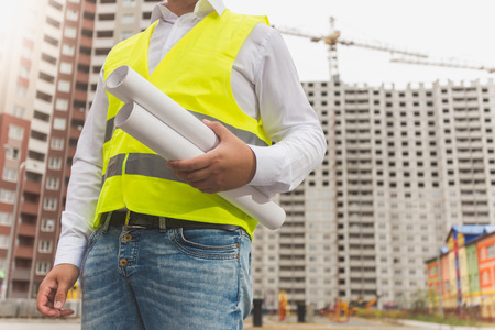 Young male foreman holding rolled blueprints Stock Photo