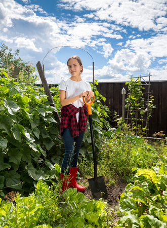 Beautiful teenage girl working on garden at farm at sunny day Stock Photo