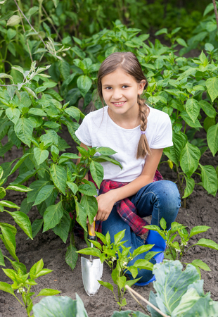 Portrait of cute teenage girl planting plants at garden