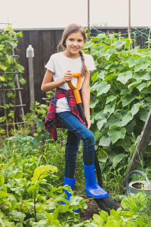 Happy girl working at garden with shovel Stock Photo
