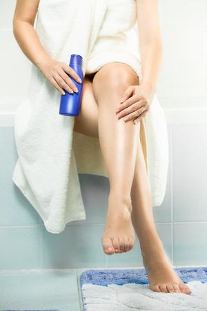 Beautiful sexy woman sitting in bathroom and applying lotion on legs after bathing Stock Photo