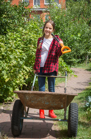 Smiling teen girl in wellies working in garden