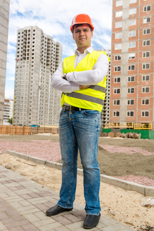 Construction engineer standing in front of buildings under construction