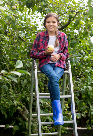Happy smiling girl picking ripe apples at garden at bright sunny day