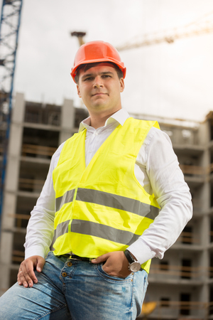 Smiling construction engineer in hardhat looking at camera Stock Photo