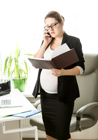 electronic book: Pregnant businesswoman talking by phone and checking documents Stock Photo