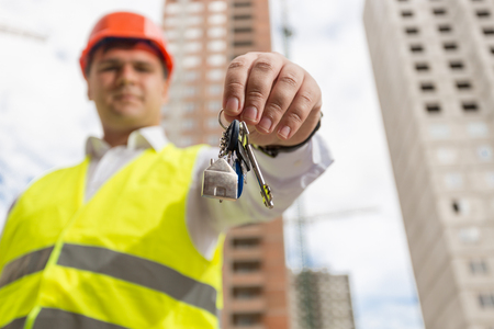 Portrait of young engineer showing keys from new home