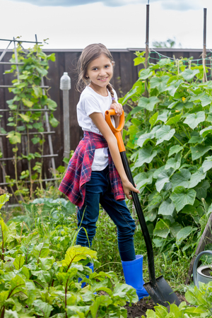 Beautiful smiling teenage girl posing at backyard garden with shovel