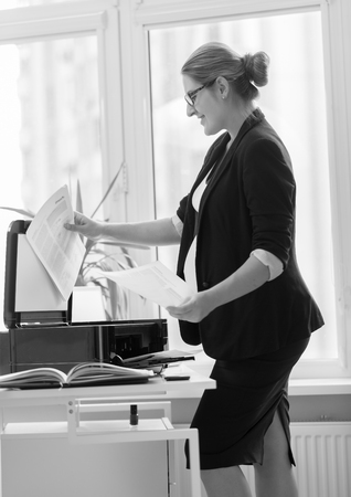 xerox: Young businesswoman in black suit making copies of documents on xerox Stock Photo