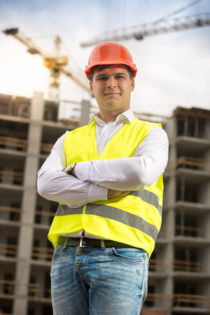 Portrait of smiling architect in hardhat standing against building under construction
