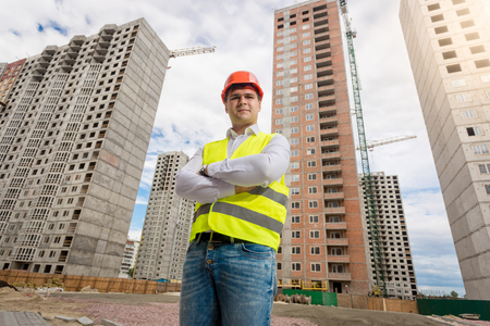 Young architect in hardhat and safety vest posing against new buildings