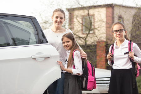 Happy mother and two girls with school bags posing at the car