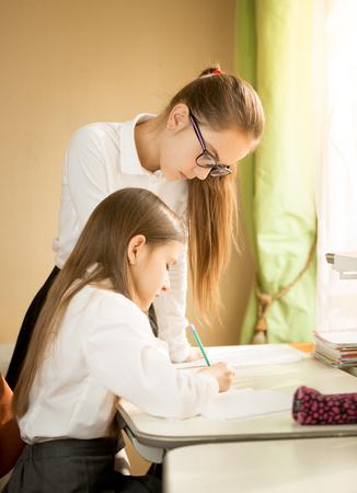 learning by doing: Elder girl helping doing homework to younger sister