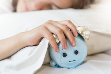 Closeup photo of young woman holding hand on alarm clock
