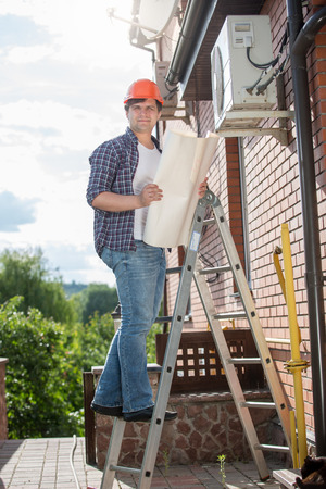 Electrician standing on high stepladder and holding plan of house